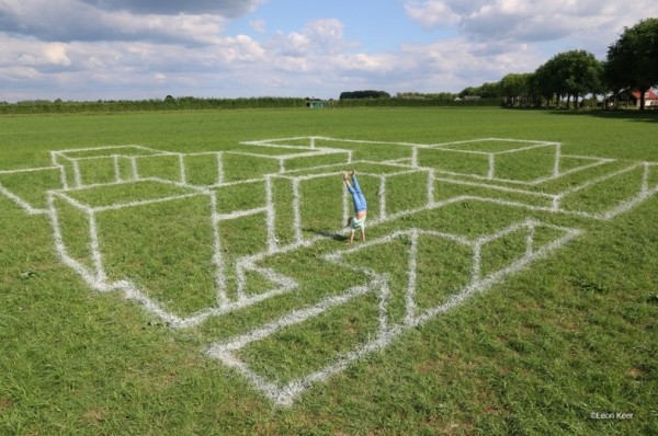Anamorphosis chalk on grass by Leon Keer
